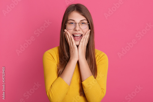 Horizontal shot of excited female wearing casual attire and spectacles, looking at camera with happy facial expression, has good news, posing against pink studio wall Canvas Print
