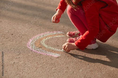 Faceless picture of little girl wearing red closing drawing colorful rainbow on asphalt road with chalk, child spending time in open air, holding piece of chalk in hands, playing in sunny day Canvas-taulu