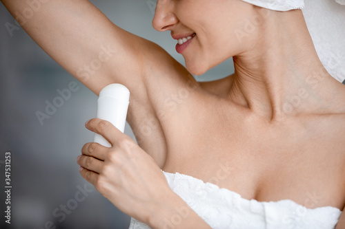 Close up woman after shower body head wrapped in white towel, raises hand applie Canvas Print