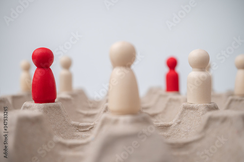 A wooden figure standing with team to influence and empowerment. Concept of leadership, successful competition winner and Leader with influence and Social distancing for a new normal lifestyle