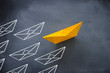 Leadership concept with paper boat on blackboard background. One leader ship leads other ships.