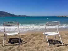 Empty Chairs On Beach Against Clear Sky