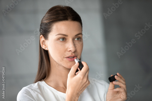 Photo Head shot 35s model with natural makeup, woman puts pink lipstick on lips looks