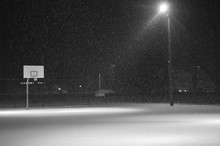 Empty Basketball Court During Snowfall At Night