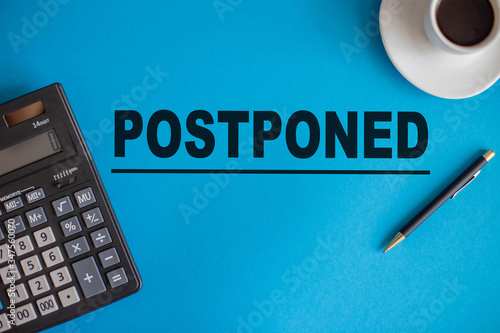Photo The word postponed is written on a blue background next to a calculator, pen, an
