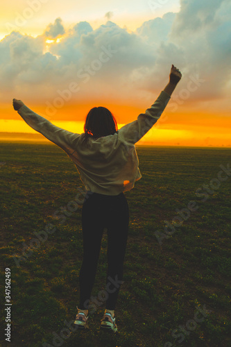 Fototapeta Young woman jumping in green field on the sunset. Beautiful girl on the nature obraz na płótnie