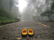 Abandoned Sandals On Country Road In Foggy Weather
