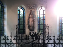 Mother Mary Statue Against Stained Glass Windows