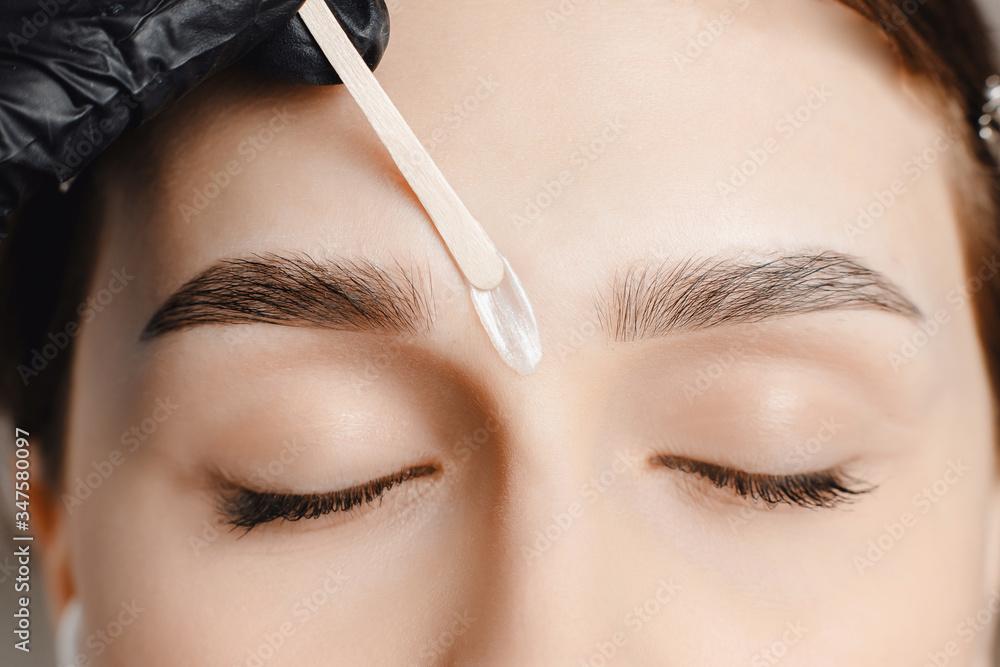 Fototapeta Master wax depilation of eyebrow hair in women, brow correction