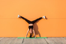Overjoyed Happy Girl With Perfect Athletic Body In Tight Sportswear Doing Yoga Handstand Pose With Spread Legs Against Wall And Showing Tongue, Having Fun. Gymnastics For Body Balance, Flexibility