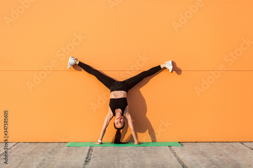 Photo Overjoyed happy girl with perfect athletic body in tight sportswear doing yoga handstand pose with spread legs against wall and showing tongue, having fun