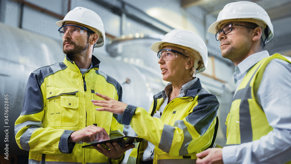 Fototapeta Three Heavy Industry Engineers Stand in Pipe Manufacturing Factory, Use Digital Tablet Computer, Have Discussion. Large Pipe Assembled. Design and Construction of Oil, Gas and Fuels Transport Pipeline