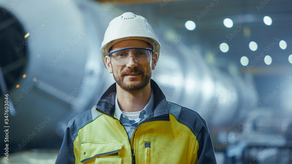 Fototapeta Portrait of Smiling Professional Heavy Industry Engineer / Worker Wearing Safety Uniform, Goggles and Hard Hat. In the Background Unfocused Large Industrial Factory where Welding Sparks Flying