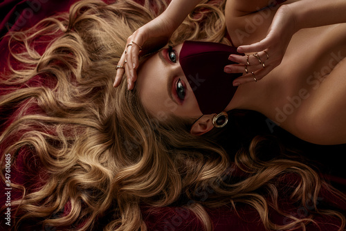 Obraz na plátne Beautiful woman with luxury blond hair, makeup, wearing protective face mask laying dark red sheets