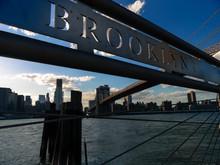Metallic Text On Railing By River Against Brooklyn Bridge