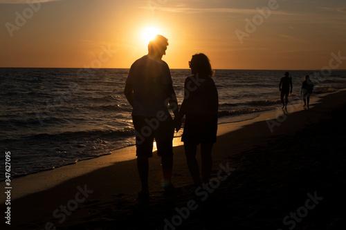 Fototapeta Para ludzi oglądający zachód słońca nad morzem. obraz