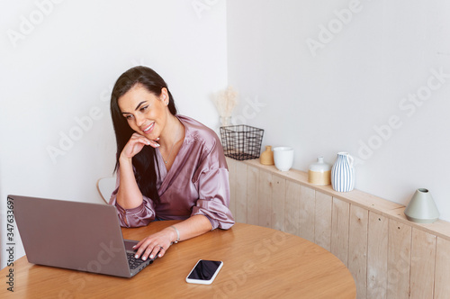Photo Affectionate woman looking at her laptop working from home in the kitchen