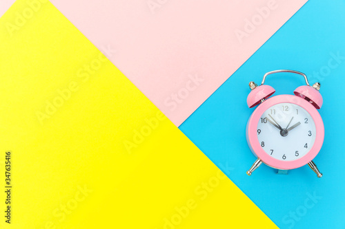 Ringing twin bell classic alarm clock isolated on blue yellow pink pastel colorful geometric background Canvas Print