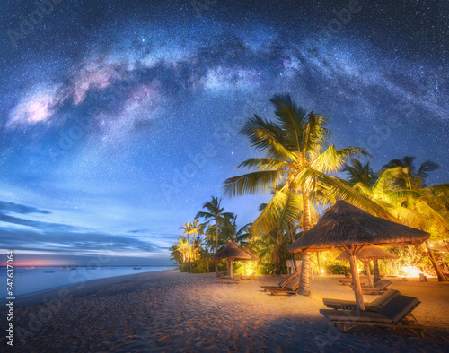 Fototapeta Milky Way over the sandy beach with palm trees and sunbeds and umbrellas at night in summer. Landscape with sea coast, beautiful blue starry sky, galaxy, green palms. Travel in Zanzibar, Africa. Space obraz na płótnie
