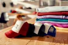More Than You Expect. Custom Apparel, Clothes Neatly Folded On Shelves. Stack Of Colorful Clothing And Baseball Cap In The Store