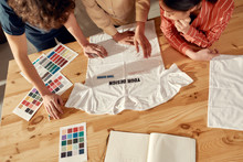 Writing For Your Success. Creative People Trying On Stickers With Text, While Discussing Logo And Design Of T-shirt. Young Man And Women Working Together At Custom T-shirt, Clothing Printing Company