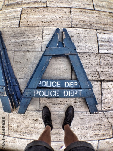 Foto Male Legs Near Trestles With Police Sign