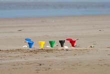 Composizione Di Posacenere Colorati Sulla Spiaggia, Circondati Da Conchiglie , Mare Sullo Sfondo