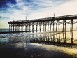 Low Angle View Of Silhouette Pier Over Beach Against Sky