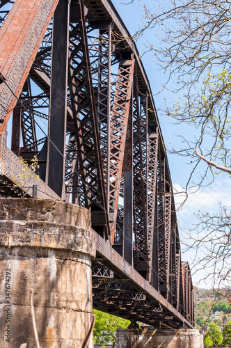 A steel railroad trestle bridge with concrete abutments on a sunny spring day in Wallpaper Mural