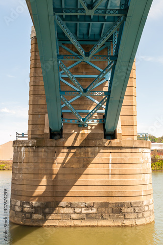 Photo A concrete abutment with metal girders of a bridge above the Allegheny River in