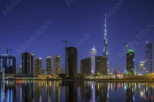Fototapety, obrazy: Burj Khalifa Amidst Buildings In Front Of Sea Against Clear Sky At Dusk