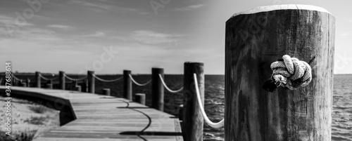 Fotografia Wooden Post On Boardwalk Against Sea