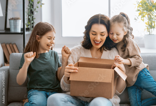 Obraz Mother and daughters are unpacking cardboard - fototapety do salonu