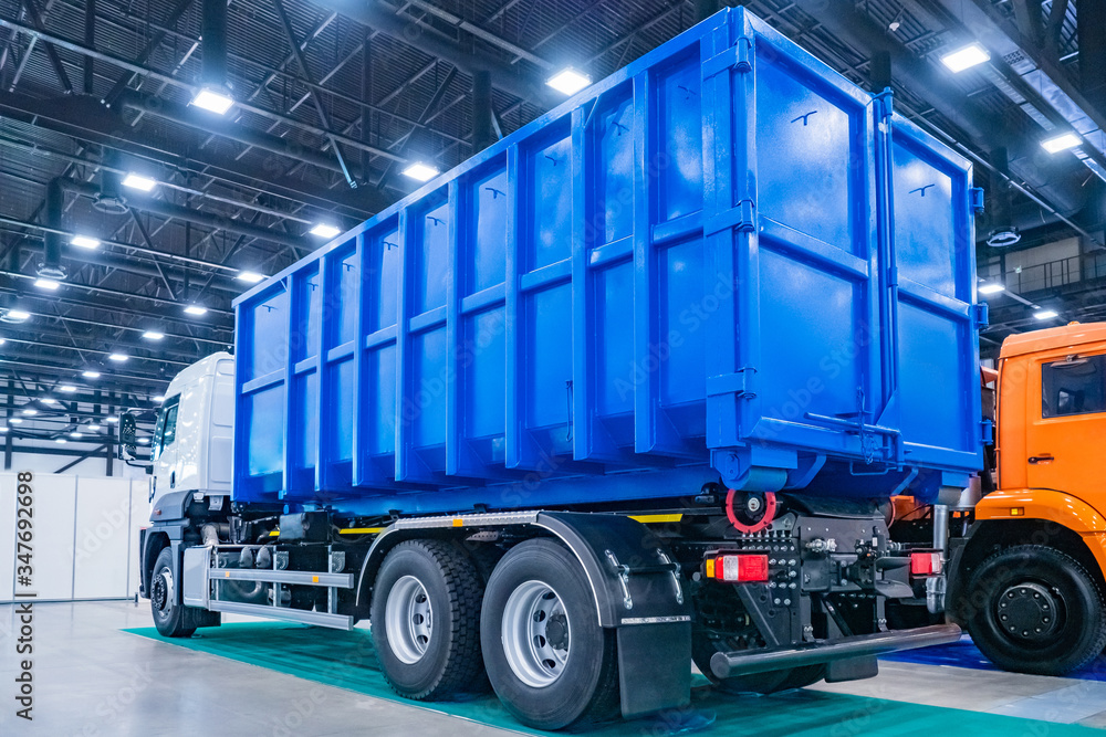 Fototapeta Equipment for public utilities. Truck for the removal of large-sized garbage. Municipal economy. The trash bin is mounted on the truck. Removal of construction debris.