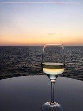 Close-up Of Wineglass Against Clear Sky At Sunset