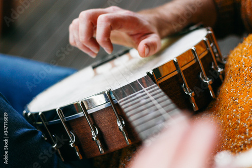 Fotografía Close up of a male banjo player relaxing on the porch, practicing clawhammer, finger picking and thumb tapping
