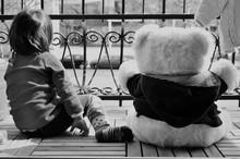 Rear View Of Boy With Teddy Bear Sitting On Footpath