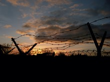 Silhouette Barbed Wire Fence On Field Against Sky During Sunset