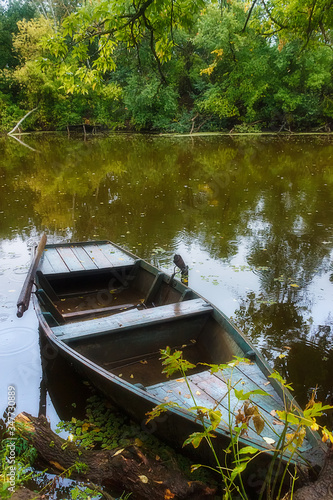 A moody rainy scene with an old wooden fishing boat near a forest covered river bank