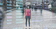 The woman in medical mask stands outdoor on holographic background. time lapse
