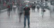 The young man in medical mask stands in crowdy flow. time lapse