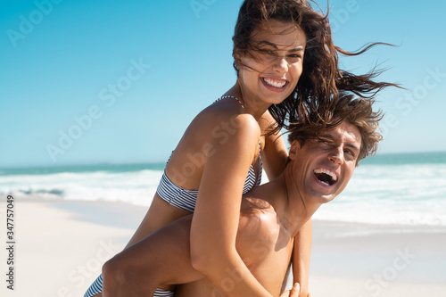 Fototapeta Beautiful woman enjoying piggyback ride at beach obraz