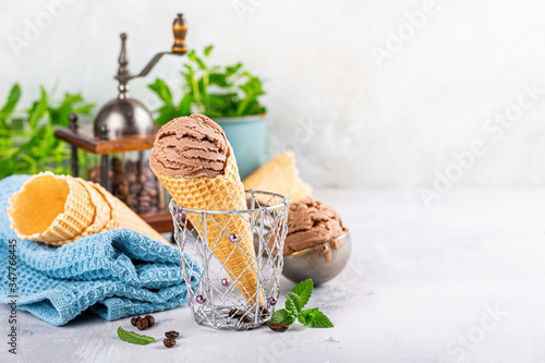 Fototapeta Delicious coffee or chocolate ice cream in waffle cone for dessert. Summer healthy food concept, lactose free. Copy space. obraz