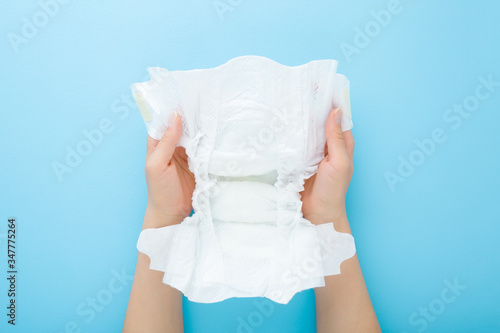 Tableau sur Toile Young mother hands holding opened white baby diaper on light blue table background
