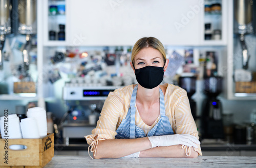 Woman owner with face mask in coffee shop  lockdown and back to normal concept.