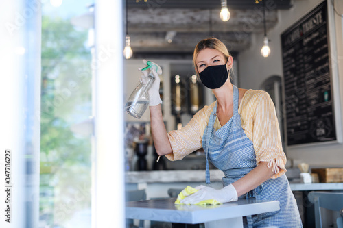 Fototapeta Coffee shop woman owner working with face mask and gloves , disinfecting tables. obraz