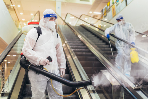 Obraz Professional workers in hazmat suits disinfecting indoor of mall, pandemic health risk, coronavirus - fototapety do salonu