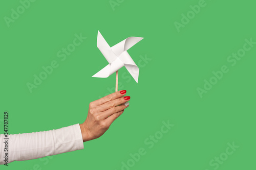 Valokuva Closeup of female arm holding pinwheel toy on stick, origami hand mill isolated on green background, showing paper windmill, white spinner to play childhood game, party favour