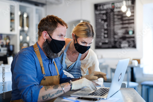 Coffee shop owners with face masks, lockdown, quarantine, coronavirus, back to normal concept Canvas Print