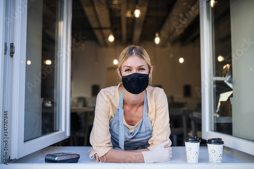 Fototapeta Woman with face mask serving coffee through window, shop open after lockdown. obraz